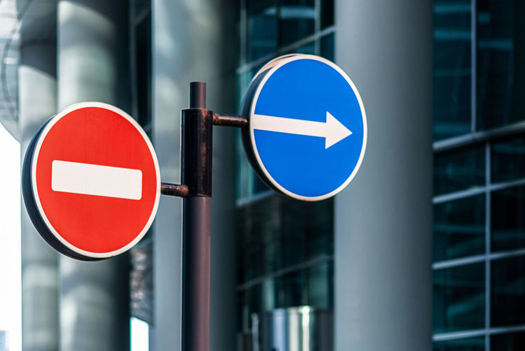 Road signs against modern glass building background, no entry and arrow traffic signs
