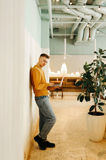 Side view of young man looking at potted plant against wall