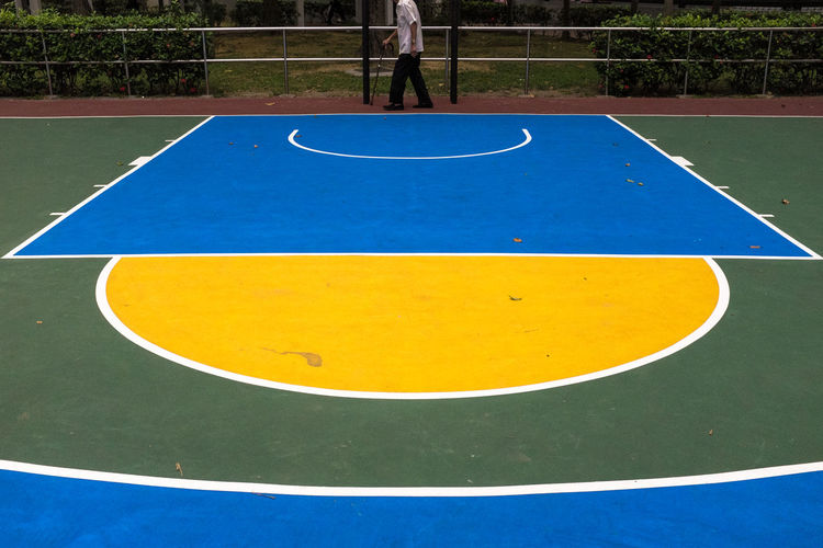 Low section of person walking by basketball court