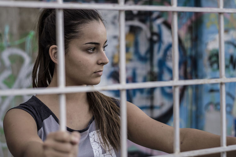 Close-up of thoughtful teenage girl seen through fence