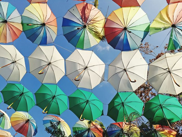 Low angle view of colorful umbrella against sky