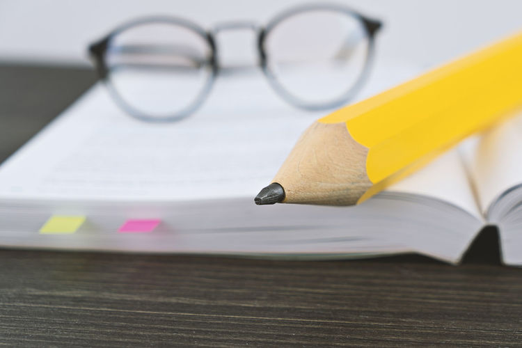 Close-up of pencil and eyeglasses on book