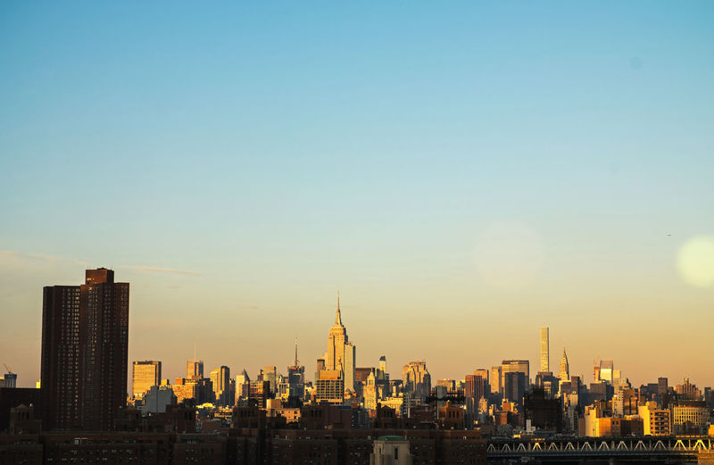 The low fall light from the setting sun makes the Manhattan skyline glow warmly. Brooklyn Bridge / New York Empire State Building NYC New York City Architecture Built Structure Day New York City Skyline Outdoors Sky View From Brooklyn Bridge
