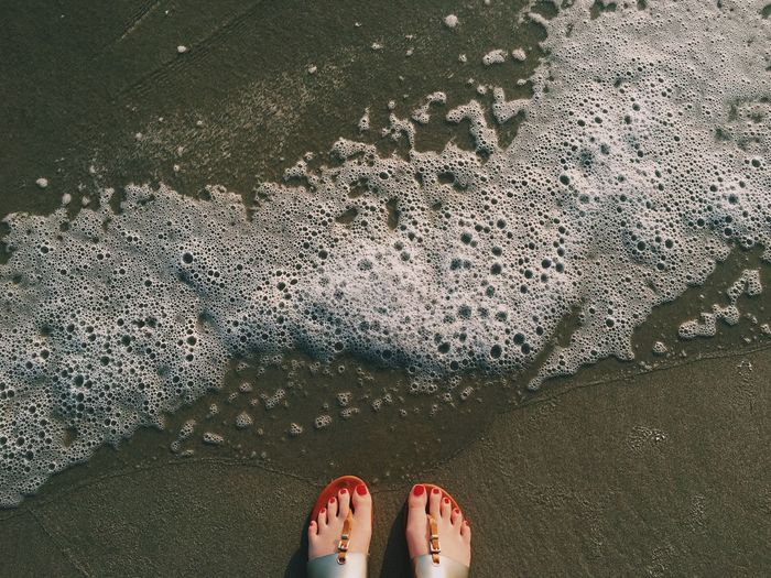 Close-up of human legs at waters edge on beach
