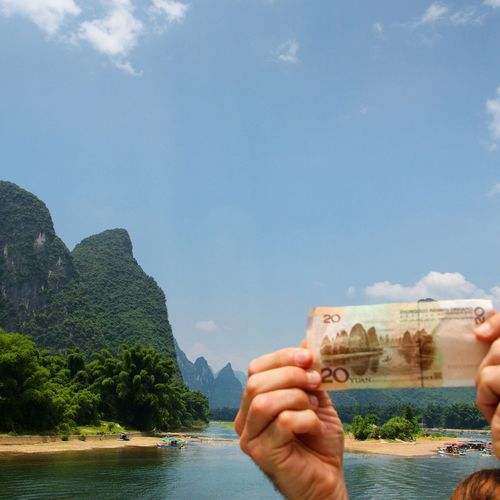 Cropped Hands Holding Paper Currency Against River And Rock Formations