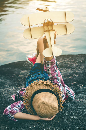 Girl holding model airplane while lying on rock by lake