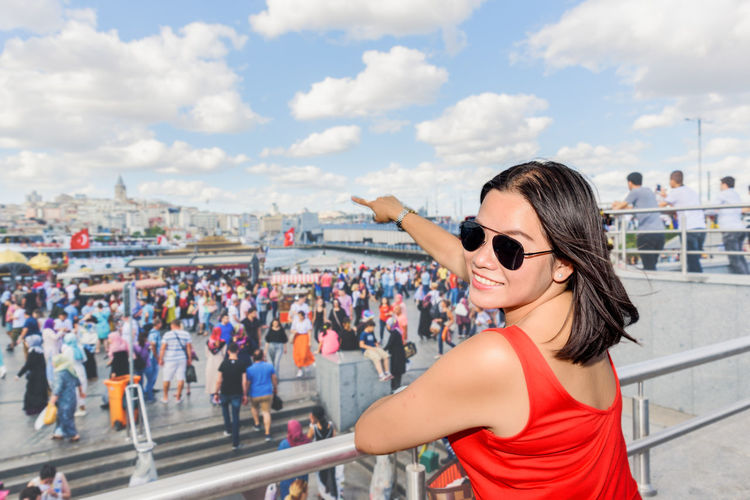 Portrait of woman wearing sunglasses pointing while standing by railing