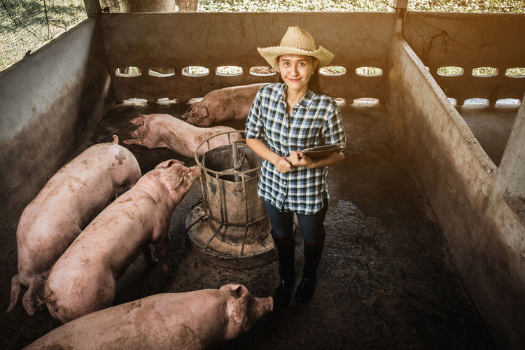 High angle portrait of female veterinarian smiling while standing in shed