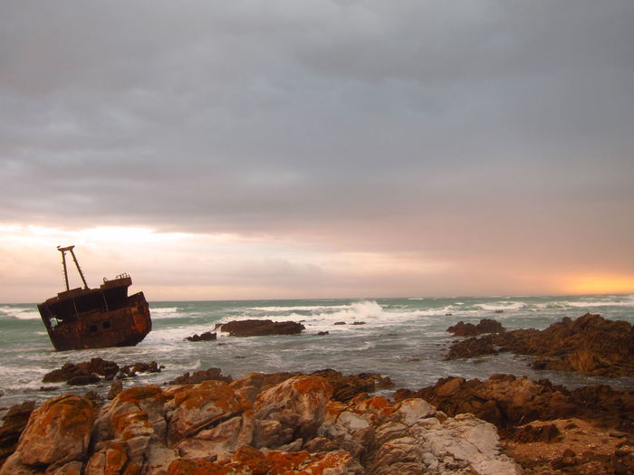 Abandoned Boat In Sea Against Sky During Sunset