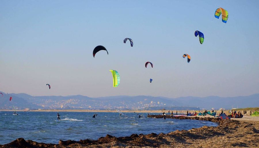 People kiteboarding in sea against clear sky