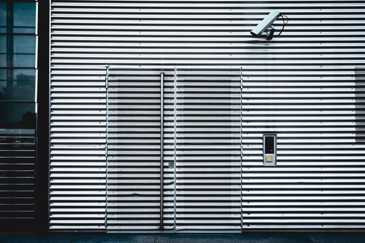 Security camera on corrugated building wall