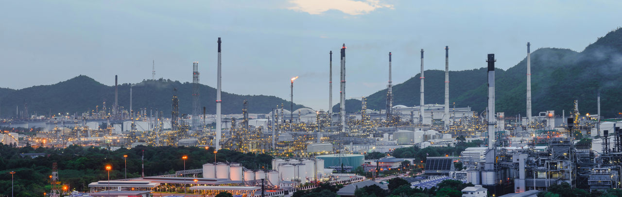 Panoramic view of industry against sky at dusk