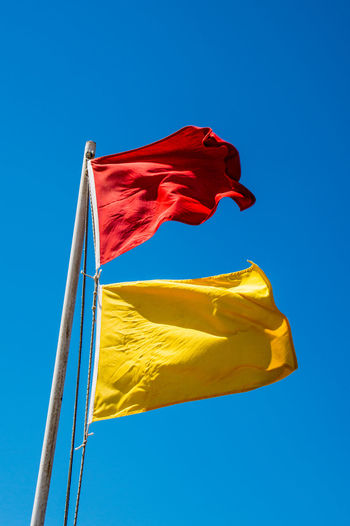 Low angle view of flags waving against blue sky