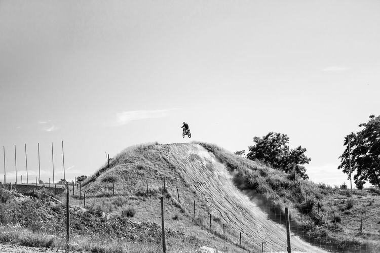 Motocross rider riding motorcycle against sky