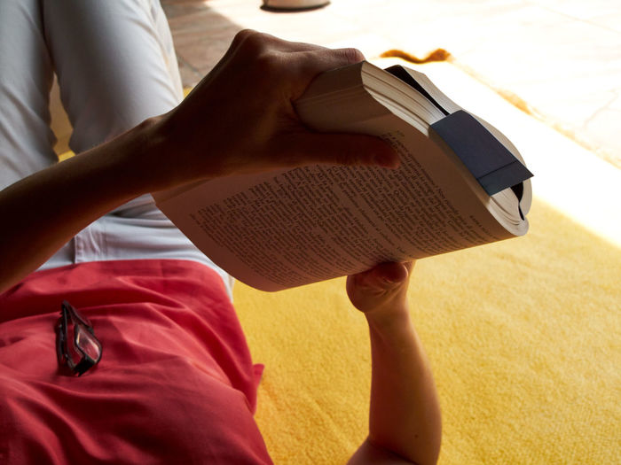 Midsection of woman reading book while lying on bed