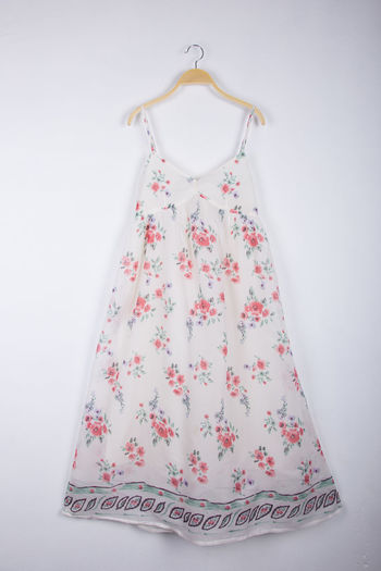 Dress hanging on coathanger against white background