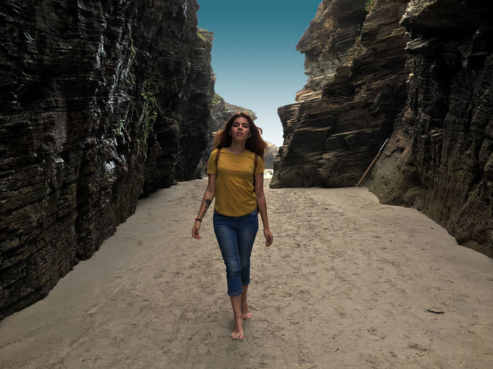Full length of young woman walking on rock