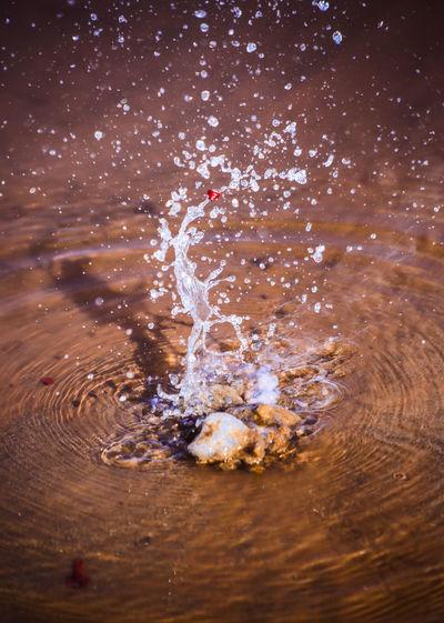 Reflection of man in water splashing