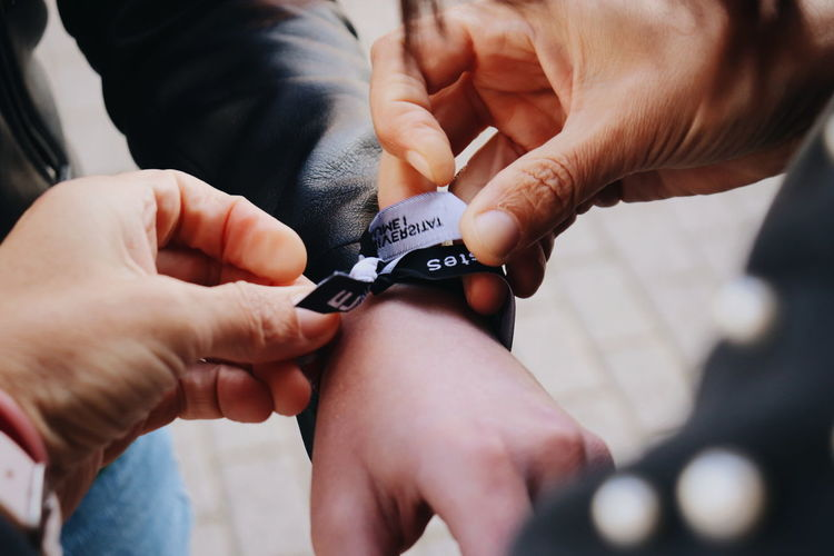 Midsection of man tying ribbon on friend hand