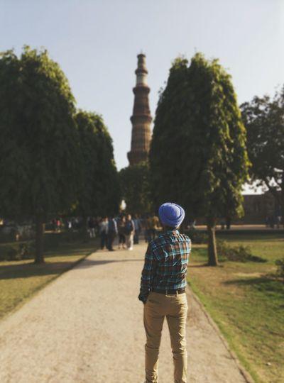 Rear view of man looking at the qutub minar