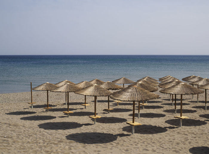 beach at Rethymno Crete with the umbrellas and loungers set out for the day Beach Beach Umbrella Holiday In A Row Outdoors Protection Sand Sea Shadows Umbrella Vacations