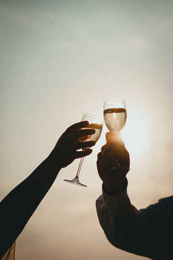 Close-up of hand holding wine glass against sky during sunset
