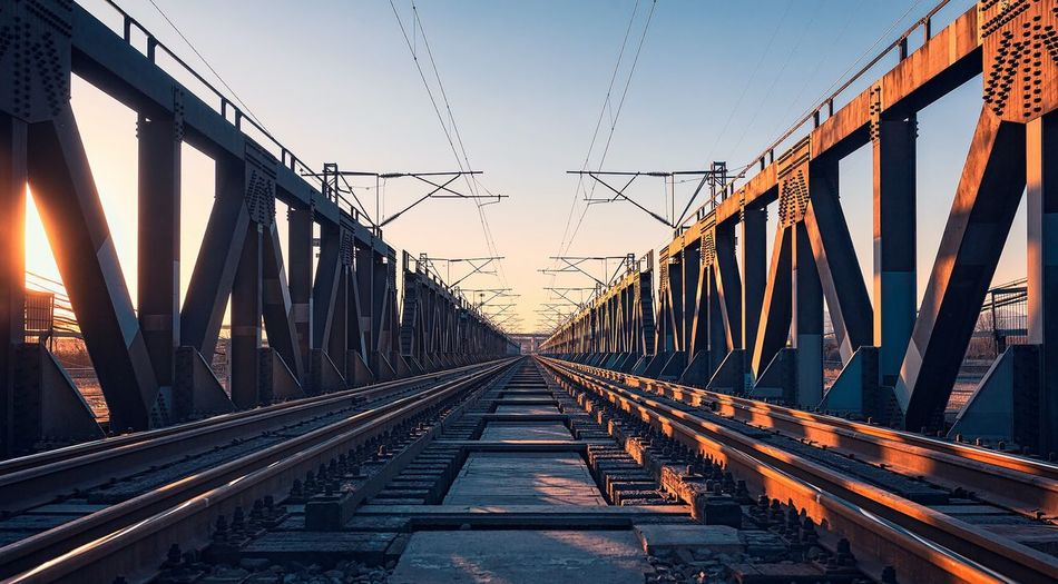 Railway bridge against sky at sunset