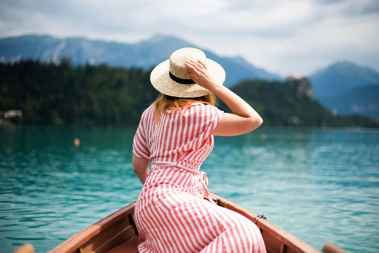 Stunning landscapes of Lake Bled, Slovenia Adult Beauty In Nature Clothing Hat Holiday Lake Leisure Activity Lifestyles Looking At View Mountain Nature One Person Outdoors Real People Rear View Scenics - Nature Sun Hat Tranquil Scene Trip Vacations Water Women