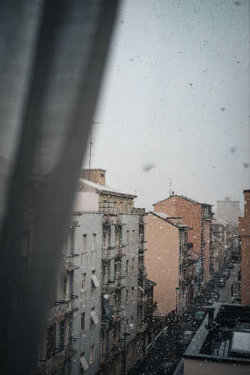 Buildings seen through window during rainy season