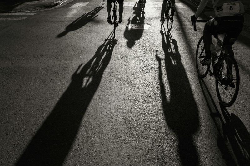 Rear view of athletes cycling on street