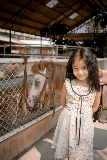 Portrait of smiling girl standing in stable