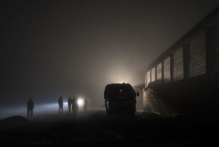 People walking by building against sky during foggy weather at night