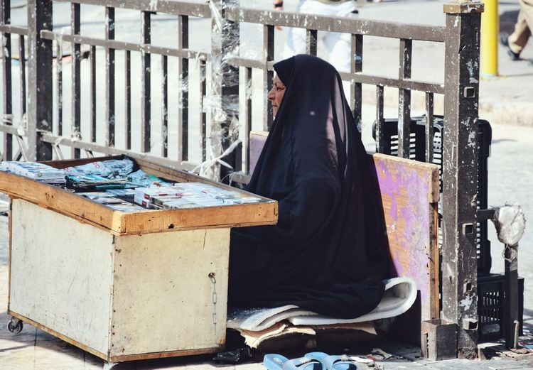 Side view of mature woman wearing hijab sitting at market stall