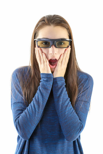 Portrait of surprised girl wearing 3-d glasses against white background