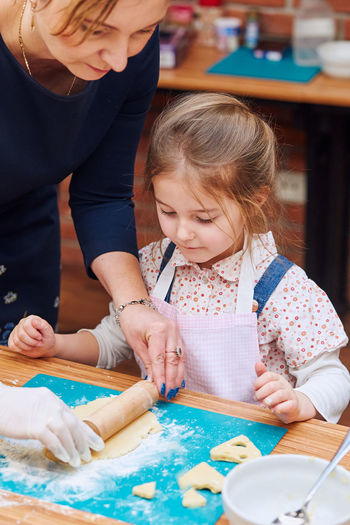 Girl looking at woman rolling dough
