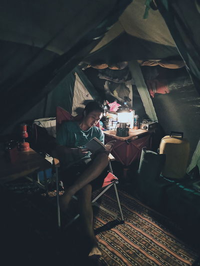 Man reading book while sitting in tent