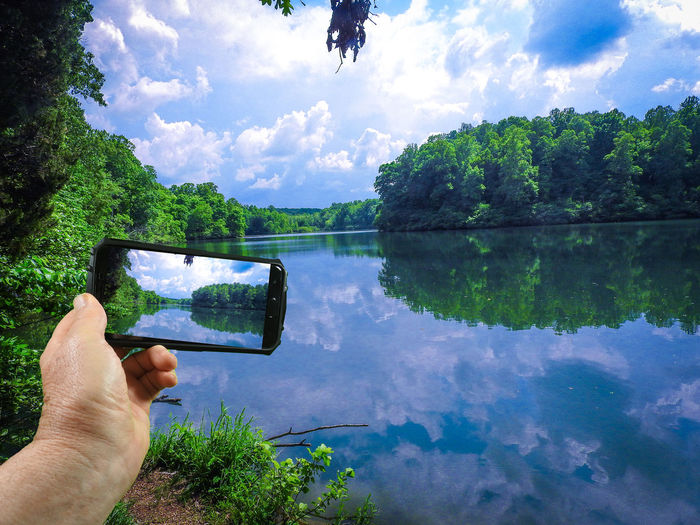 Midsection of man photographing by lake against sky