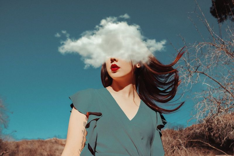 Digital Composite Image Of Young Woman And Cloud Against Sky