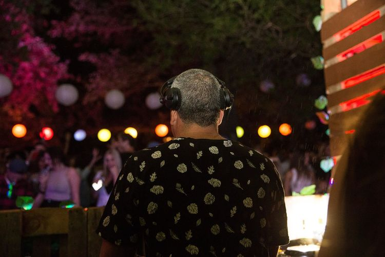 Rear view of man sitting in illuminated stage at night