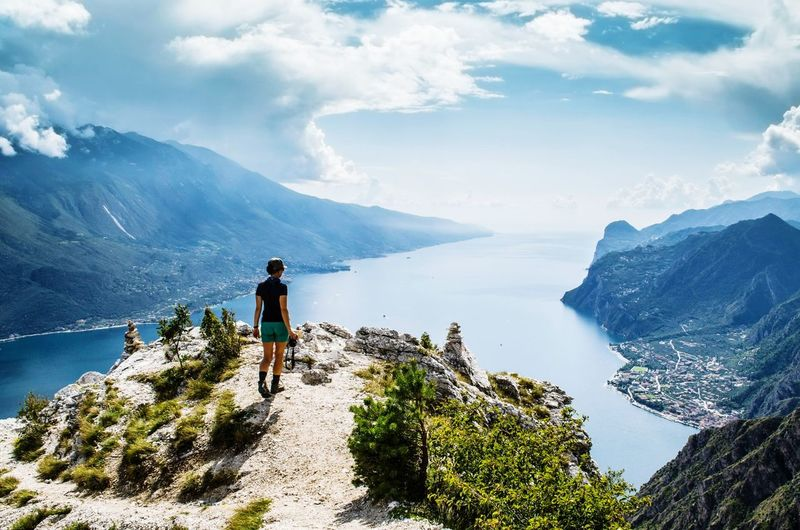 Rear view of mature woman looking at lake while standing on mountain against sky