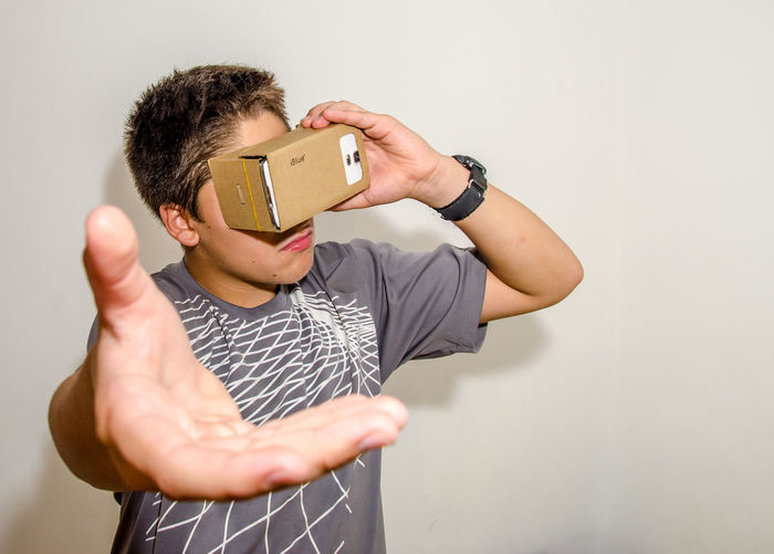 Cardboard Cardboard Box Composition Confidence  Google Cardboard Holding Human Body Part Human Finger Human Hand Indoors  Internet Lifestyles Men Person Perspective Real People Serious Studio Shot Technology Young Men Youtube