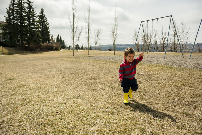 Happy playing outdoors Boy Casual Clothing Child Childhood Day Grass Happy Lifestyle Nature Outdoors Park Playground Rainboots Rubberboots Smile Sweater Toddler  Wellington Boots