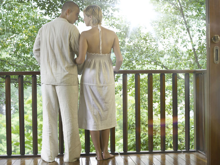 Man and woman standing at the porch Adults Only Happiness Holiday Love Romance Valentine's Day  Adults Only Bonding Caucasian Couple - Relationship Day Full Length Honeymoon Leisure Activity Lifestyles Men People Relax Resort Standing Togetherness Two People Vacation Young Adult Young Women