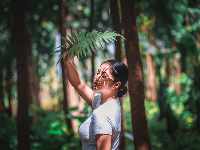 Midsection of woman standing by tree in forest
