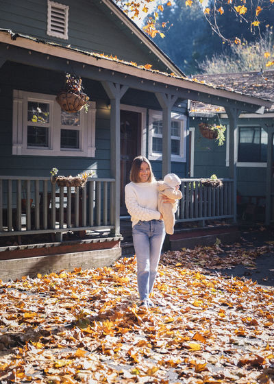 Full length of woman standing by building during autumn