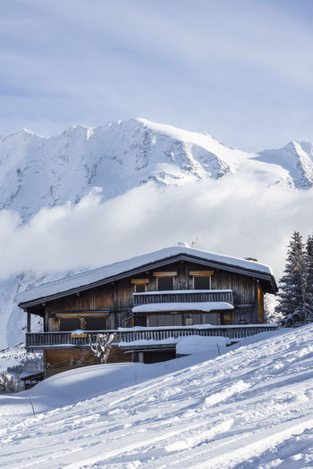 Snow covered house and mountains against sky