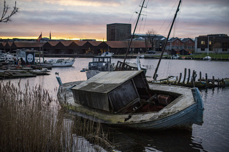 Fishing boats moored at harbor against sky during sunset