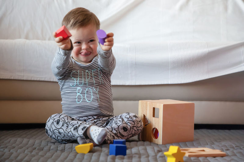 Babyboy Baby Bed Casual Clothing Child Childhood Cute Down Syndrome Flooring Full Length Furniture Home Interior Indoors  Innocence Lifestyles Mental Health  One Person Playing Real People Sitting Toy Young