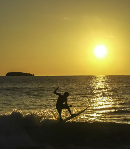Surf Beach Beauty In Nature Horizon Horizon Over Water Land Leisure Activity Lens Flare Nature One Person Orange Color Outdoors Real People Scenics - Nature Sea Silhouette Silhouette Surfboard Sky Sport Sun Sunlight Sunset Surfing Water