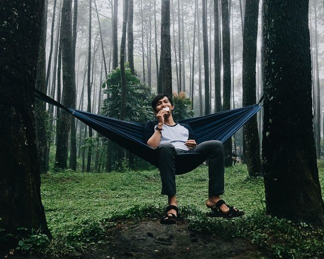 Portrait of young woman sitting on hammock in forest